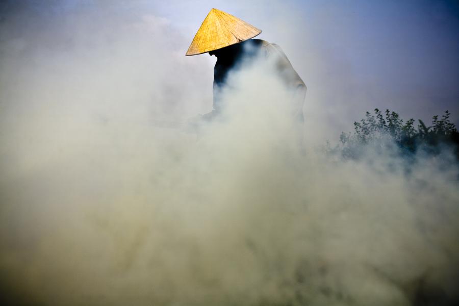 Um agricultor queimando resíduos da plantação e se preparando para a época de cultivo pós-enchentes em Hanoi, Vietnã.
