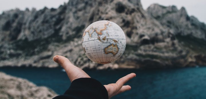A small globe floating in the air above an open palm